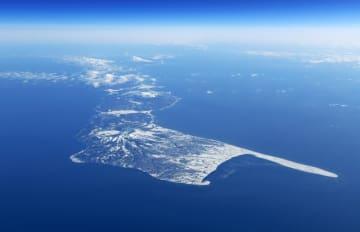 北海道標津町の上空から望む国後島。奥にはうっすらと択捉島が見える=1月30日