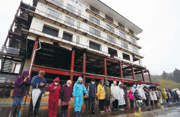 震災遺構「たろう観光ホテル」の前で手をつなぎ、黙とうする地元の人たち=11日午後2時46分、宮古市田老