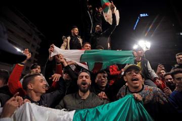 アルジェの道路で、アルジェリアのブーテフリカ大統領の出馬撤回を喜ぶ人々=11日(ロイター=共同)