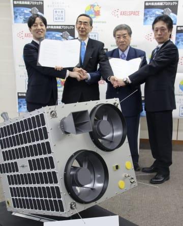 超小型人工衛星(手前・模型)の製造や試験を共同実施する、福井県の県民衛星技術研究組合と宇宙関連ベンチャー企業アクセルスペースの契約締結式=12日午後、福井県庁