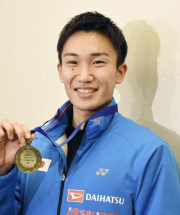 羽田空港に帰国し笑顔でメダルを持つ桃田賢斗=12日
