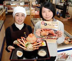 香住ガニをふんだんに使った「マルヤ丼」とフェスタをPRする長谷川加奈子さん(左)ら=香美町香住区香住