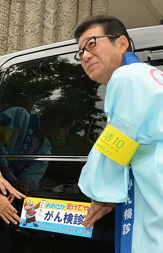 タクシーにステッカーを貼る松井知事=昨年10月、大阪府庁
