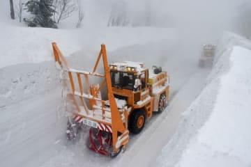 壁面を削り、雪の回廊を形づくるロータリー車=12日午前、八甲田・十和田ゴールドライン