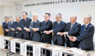 調印後、握手する伊藤市長(左から4人目)と8改良区の代表