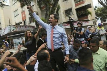 12日、ベネズエラ・カラカスで、支持者らに囲まれるグアイド国会議長(AP=共同)