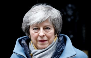 13日、ロンドンの首相官邸の外を歩くメイ首相(ロイター=共同)