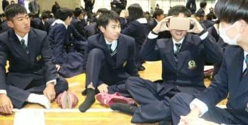 VRゴーグルを使った動画で自転車事故を疑似体験する生徒=13日、大分市の大分中・高校