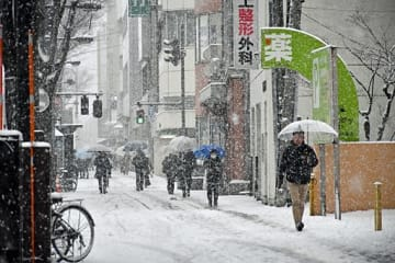 雪が降りしきる中、足早に先を急ぐ市民ら=14日午前7時45分ごろ、青森市古川
