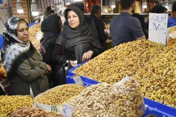 13日、イラン・テヘランのバザールにあるナッツ販売店で品物を選ぶ女性客ら(共同)