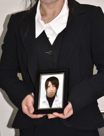 金沢泰良さんの遺影を手にする母親=14日午後、大津市