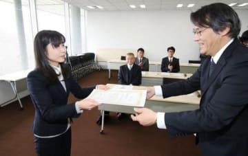 加賀会長(右)から表彰状を受け取る朝日小の担当者