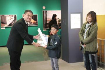 主催者から記念品を受け取る緒方奏斗君(中央)と母親の瞳さん(右)=14日午前、宮崎市・県総合博物館