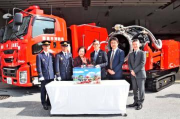 トミカになったハイパーミストブロアー車を城間幹子市長(左から3人目)に贈る小島一洋社長(同4人目)=14日、那覇市消防局