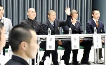 キャプテントークで照れくさそうに挙手し、選手宣誓を希望する啓新高校の穴水芳喜主将(中央)=3月14日、大阪市