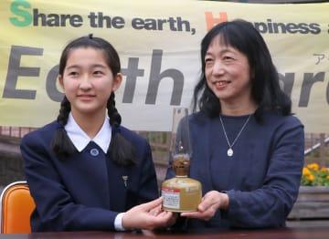 「平和の火」を手にする新海さん(右)と岡田さん=長崎市役所