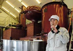 蒸留器を前に説明する松本紀之さん=神戸ワイナリー