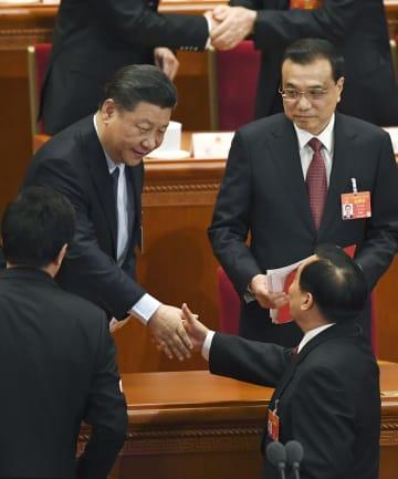 中国全人代の閉幕式を終え、幹部と握手を交わす習近平国家主席(左上)。右上は李克強首相=15日、北京の人民大会堂(共同)