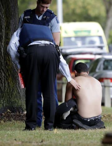 15日、ニュージーランド・クライストチャーチのモスクの外で座り込む男性に声をかける警官(AP=共同)