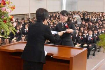 名木田学長代行(左)から卒業証書を受け取る卒業生代表