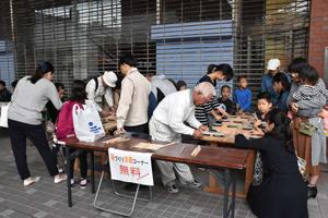 商店街で開かれた工芸体験コーナーで箸作りを体験する市民たち