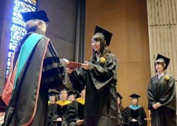 九州ルーテル学院大の卒業式で、広渡純子学長(左)から卒業証書を受け取る卒業生=15日、熊本市中央区