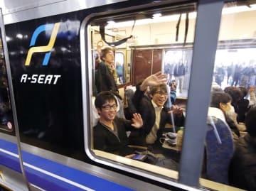新快速の一部に導入された有料座席「Aシート」の車窓から手を振る乗客ら=16日午前、JR新大阪駅