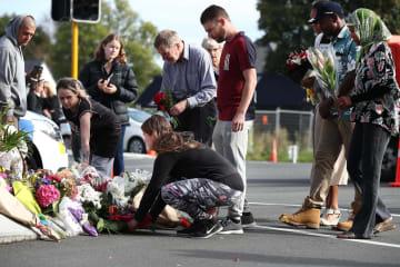 16日、銃乱射事件の起きたヌール・モスクがある通りで、犠牲者に花を手向ける地元の住民ら=ニュージーランド・クライストチャーチ(ゲッティ=共同)