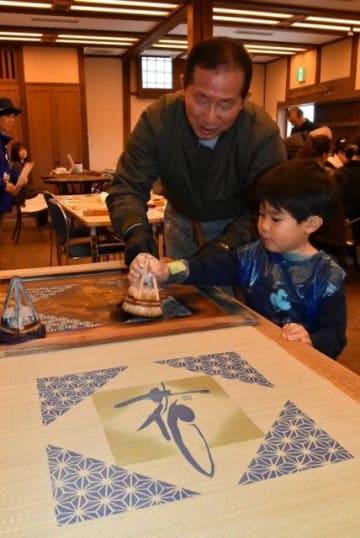 はけを使い、染料で図柄を刷り込む捺染体験を行う子ども=倉敷物語館
