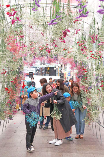 花のトンネルを飾り付ける子どもたち=長崎市、ベルナード観光通り