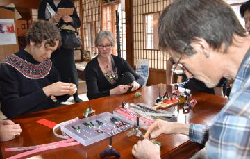 1回目のツアーでクラフトテープを使った内裏びな作りに挑戦する参加者=北茨城市平潟町の「ぎゃらりーさらま・ぽ」(2月27日)