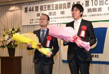 花束を受け取った渡辺棋王(左)と対局者の広瀬竜王=16日午後6時35分、宇都宮グランドホテル