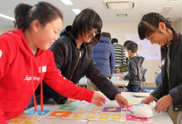 授業体験会でパネルを並べて指示通りにロボットを動かす小学生=長崎県佐世保市常盤町、市中央公民館