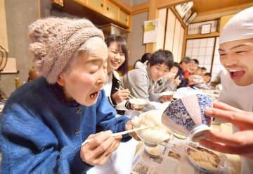 おかゆが次々と盛られ、悲鳴を上げる女性=3月16日夜、福井県勝山市遅羽町北山