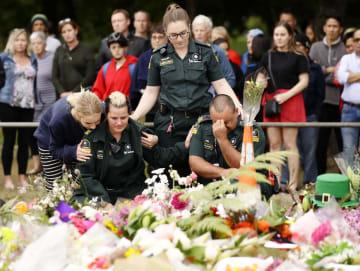 銃乱射事件があったヌール・モスクの近くで、犠牲者を悼む医療関係者ら=17日、ニュージーランド・クライストチャーチ(共同)