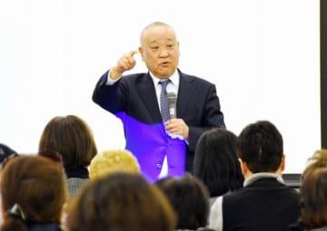 仮想通貨「WFC」について説明する発行会社社長。テキシア社に出資した人ら100人が集まった=3月16日、福井県福井市のフェニックス・プラザ