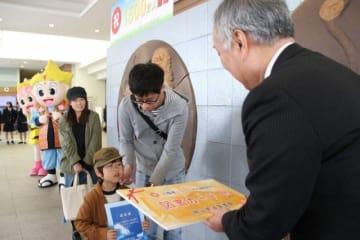 鍵本教育長(右)から記念の図書カードを贈られる上田さん一家