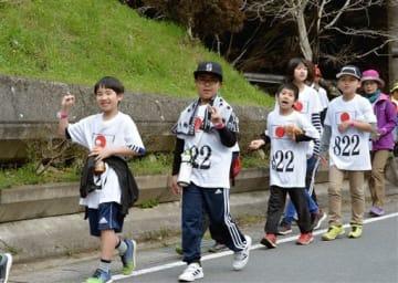 金栗四三のユニホームをまねたTシャツを着て、金栗の通学路を歩く子どもたち=和水町