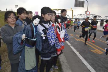 人形の手を振ってエールを送る平成座の座員=徳島市の吉野川橋北詰め
