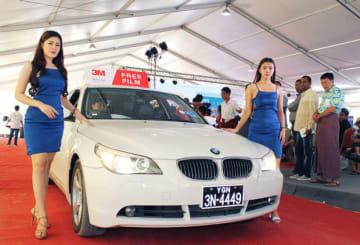 競りに参加する客のすぐ脇を、実物の車が移動したミャンマー初のカーオークション=17日、ヤンゴン(NNA撮影)