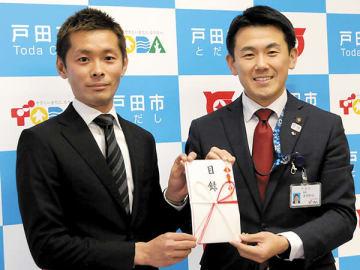 菅原文仁市長に寄付の目録を手渡した黒井達矢さん(左)=戸田市役所(市提供)
