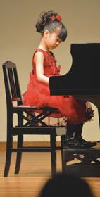ステージで堂々とピアノを演奏し、練習の成果を発揮した子ども