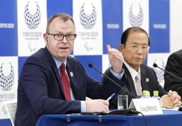 記者会見するIPCのクレイグ・スペンス広報部長。右は大会組織委の武藤敏郎事務総長=7日午後、東京都港区