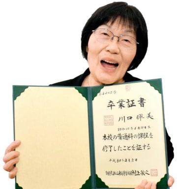 念願の高校卒業証書を手にし、満面の笑みを浮かべる川口さん