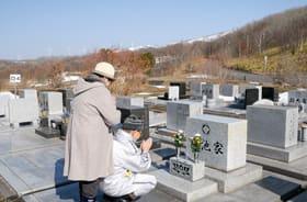 墓前で祈りをささげる夫婦=18日午前9時半ごろ、室蘭市望洋台霊園