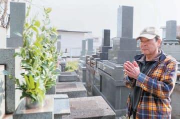 墓参りに訪れ、手を合わせる男性=18日午前、大分市の上野ケ丘墓地公園、撮影・仲道裕司