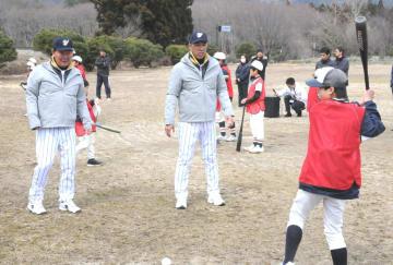 子どもに打撃指導する東尾さん(左)と和田さん