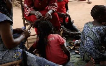元子ども兵士だった女の子の髪を結う女性たち。© Alex McBride/MSF