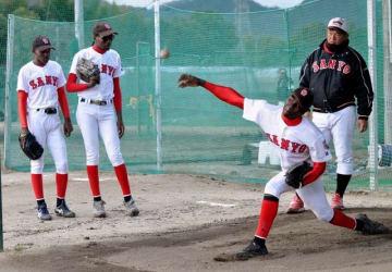 山陽高球場で練習に励むジンバブエの選手と堤尚彦監督(右奥)