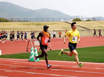 ワイナイナさんと走る参加者=長崎市総合運動公園かきどまり陸上競技場